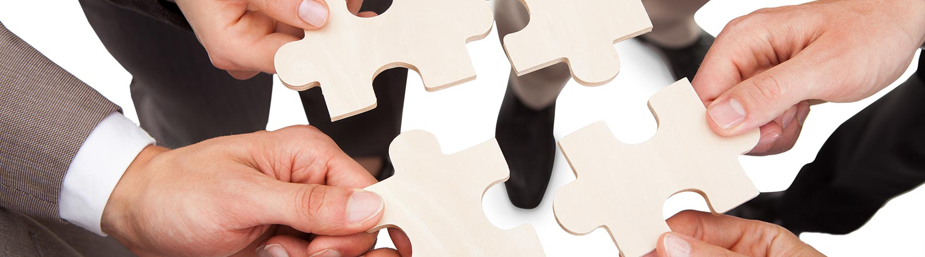 four people holding puzzle pieces together